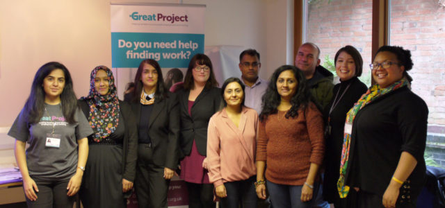 A group of participants pose with employment support officers in from of a roller banner