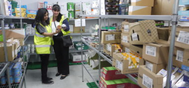 Two people look at clipboard, in the Fareshare warehouse