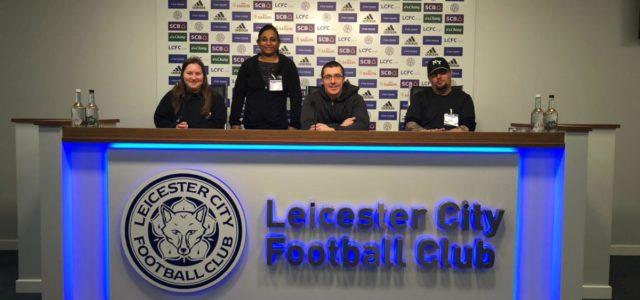 Participants pose behind Leicester City Football Club press bench for players and manager